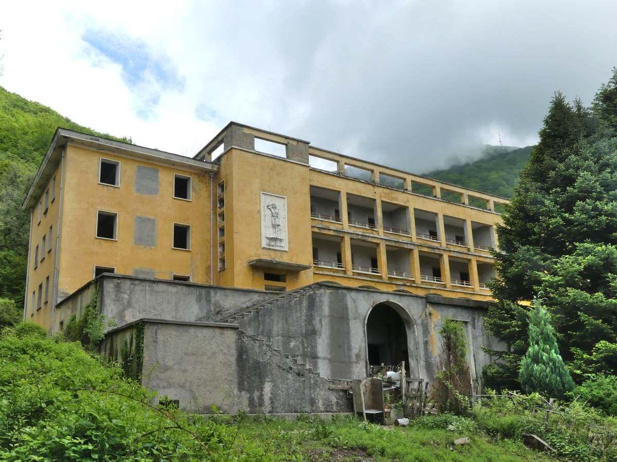 Runtergekommenes grau-gelbes Gebäude.