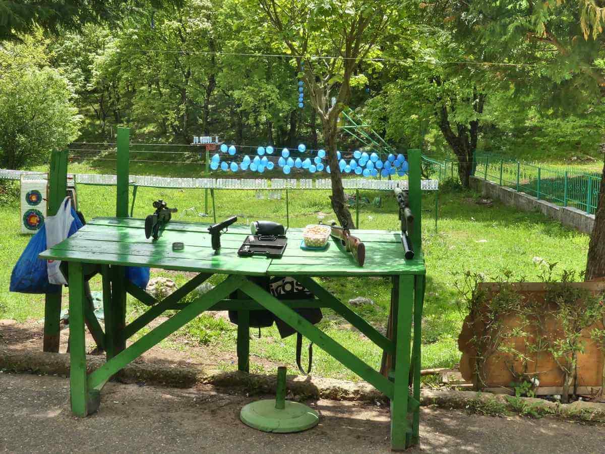 Grüner Holztisch, auf dem Gewehre und Pistolen bereit liegen.