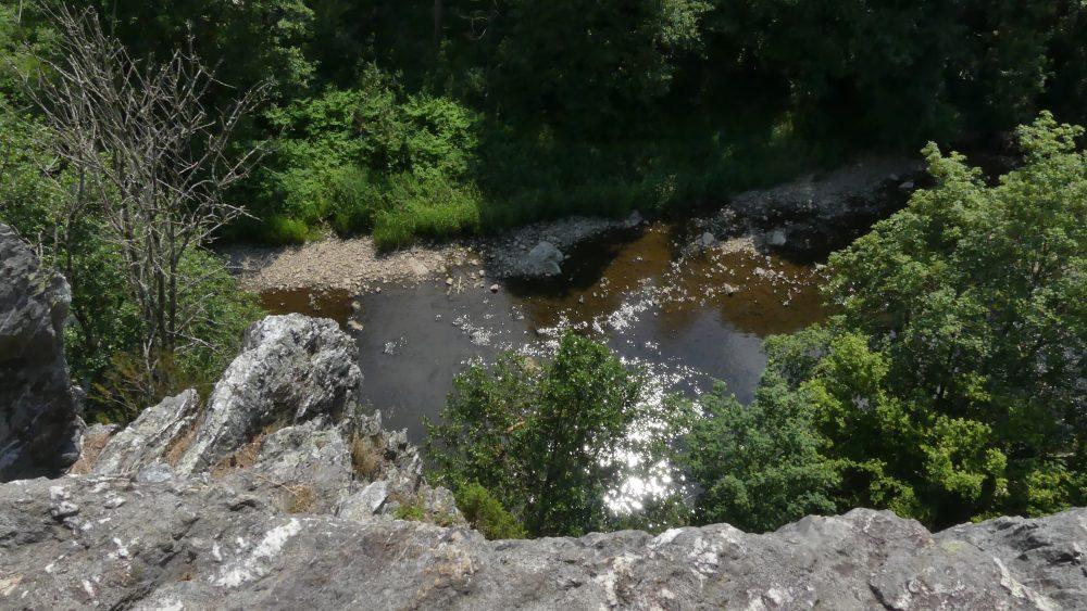 Blick an der Felswand hinunter bis zum Fluss.