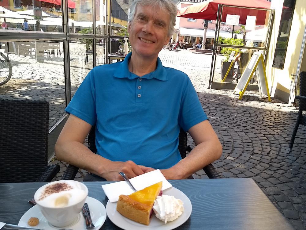 Marcus vor Kaffee und Kuchen am Tisch.