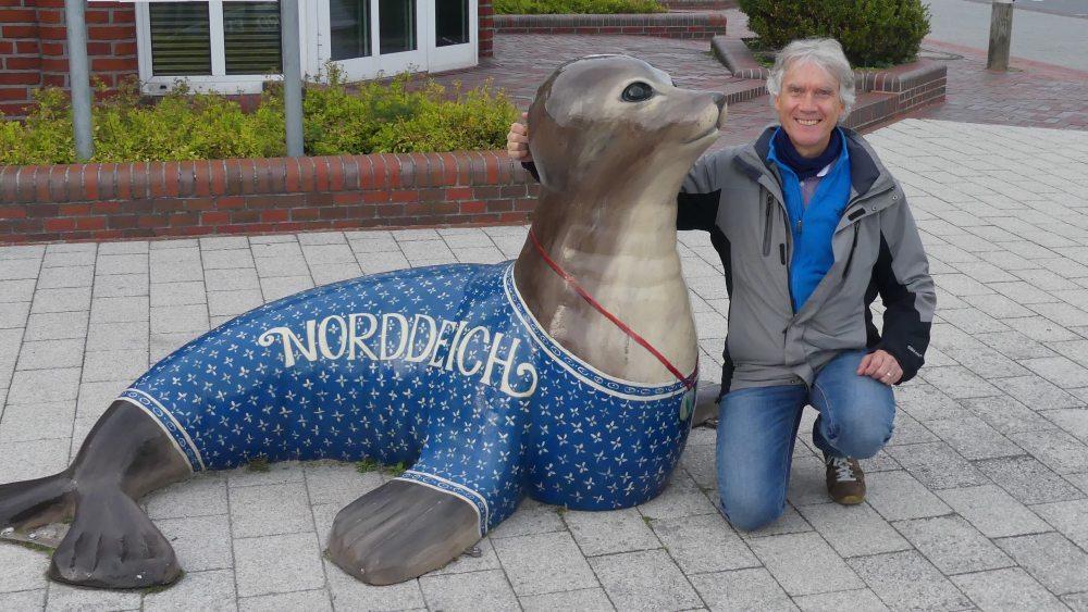 Marcus neben einer großen Seehundfigur.