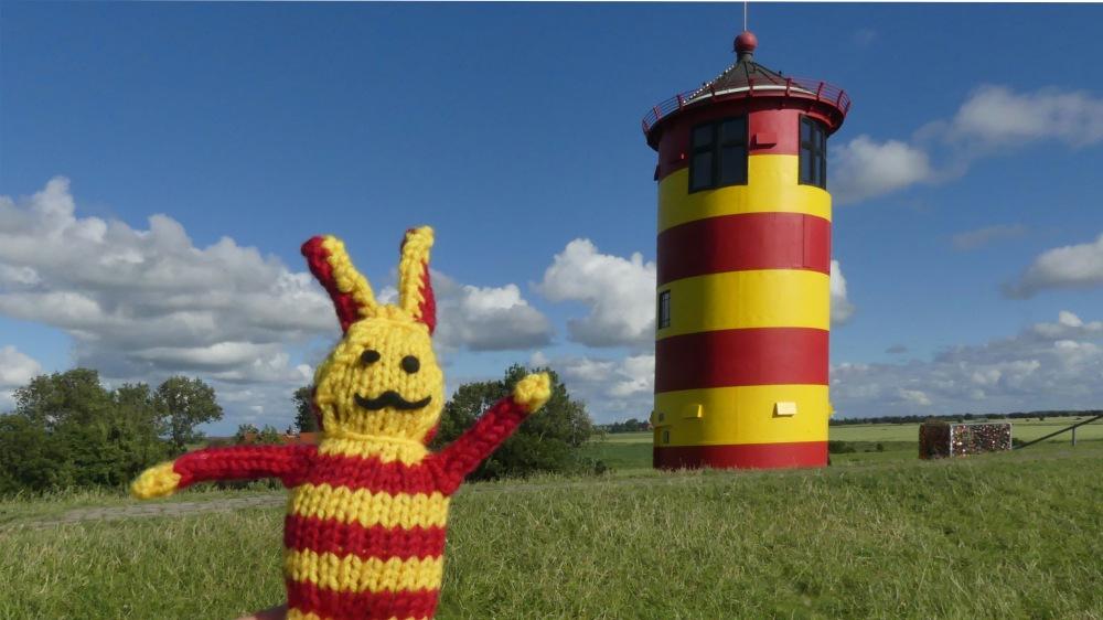 Rot-gelber Reise-Ringel neben rot-gelbem Leuchtturm.