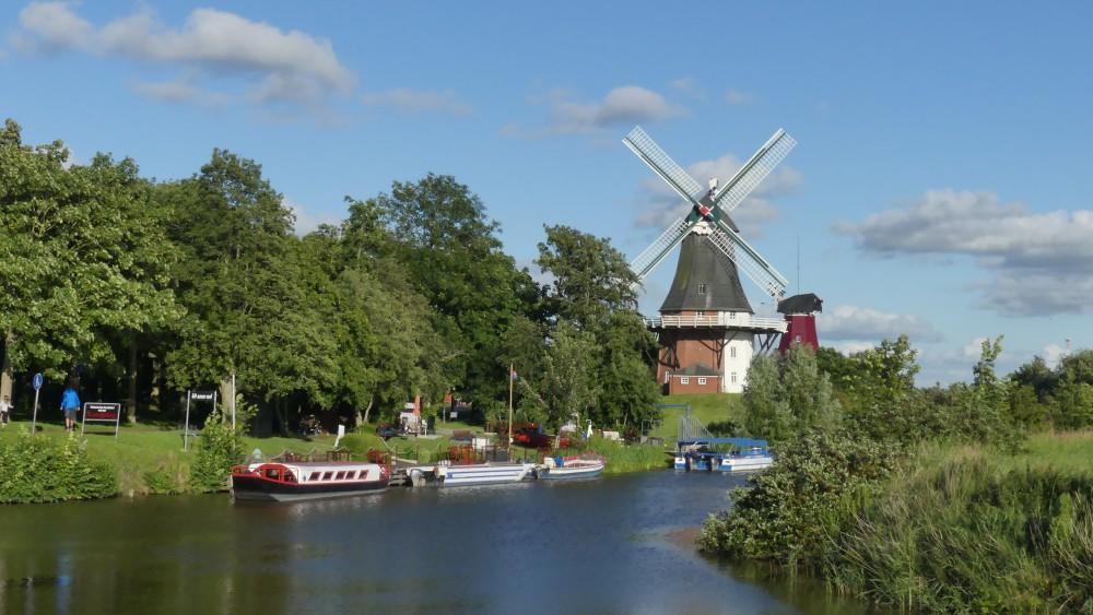 Wasserkanal mit zwei Windmühlen am Rand.
