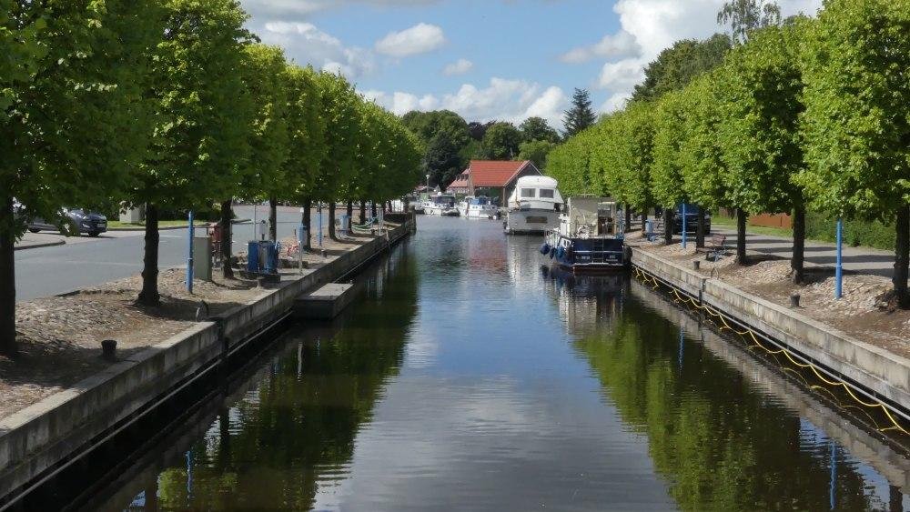 Kanalartiger Hafen auf beiden Seiten von grünen Bäumen gesäumt.
