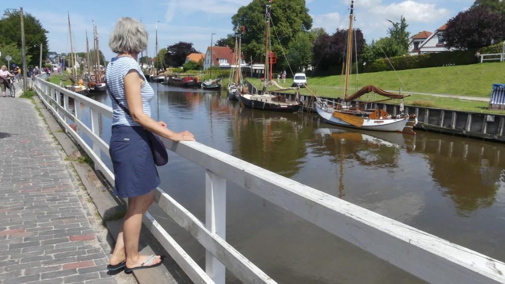 Gina steht am Geländer am Wasser.