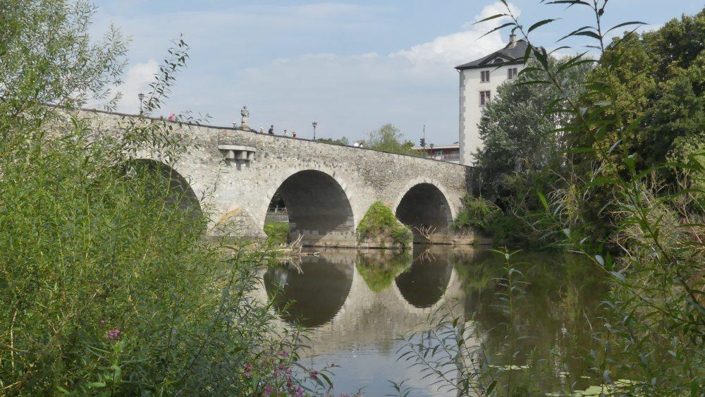 Brücke mit runden Bögen spiegelt sich in der Lahn.