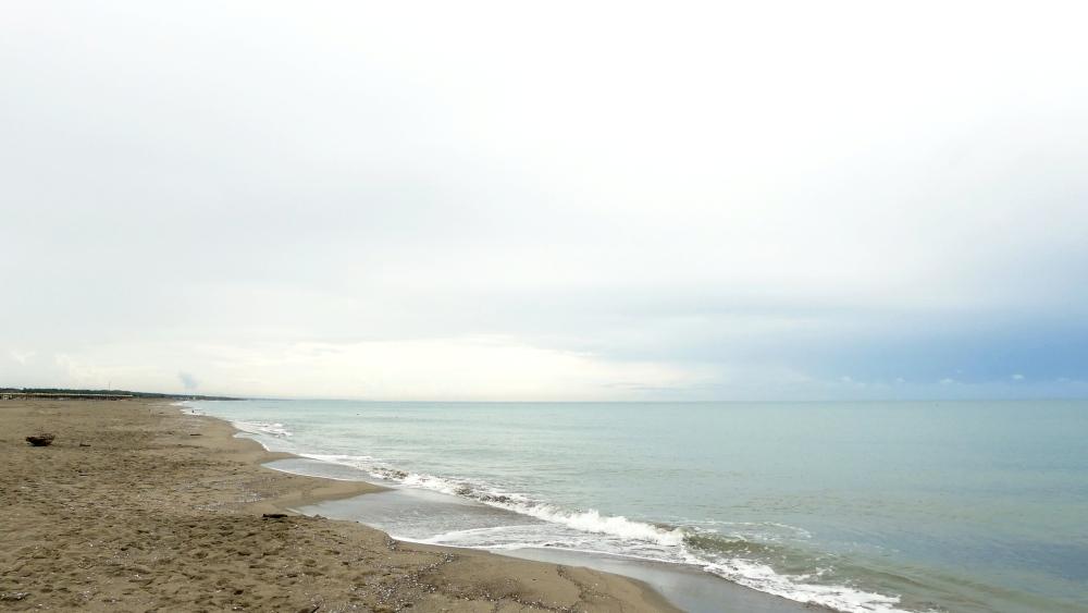 Sandstrand und Meer unter Wolkendecke.