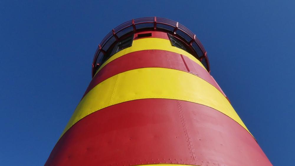 rot-gelb geringelter Leuchtturm vor blauem Himmel.