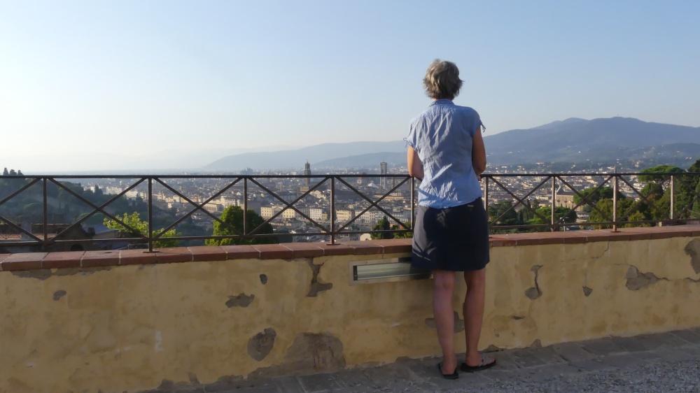 Gina steht an einem Geländer und blickt über eine Stadt.