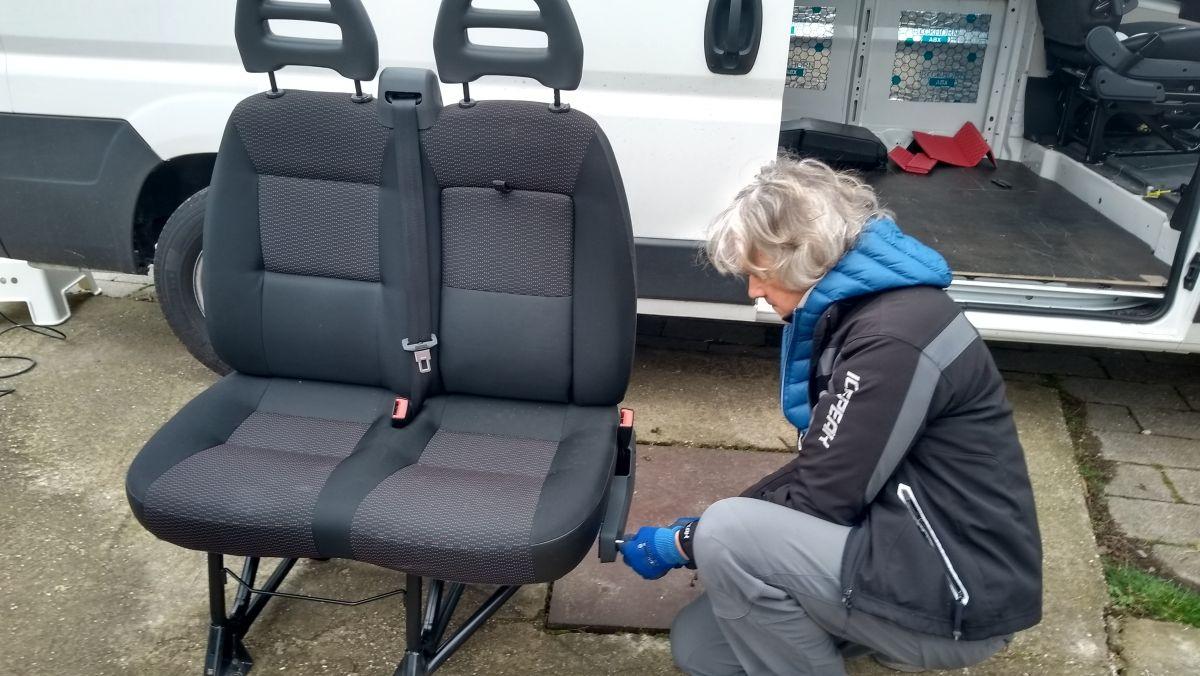 Marcus schraubt an der Doppelsitzbank, die vor dem Kastenwagen steht.
