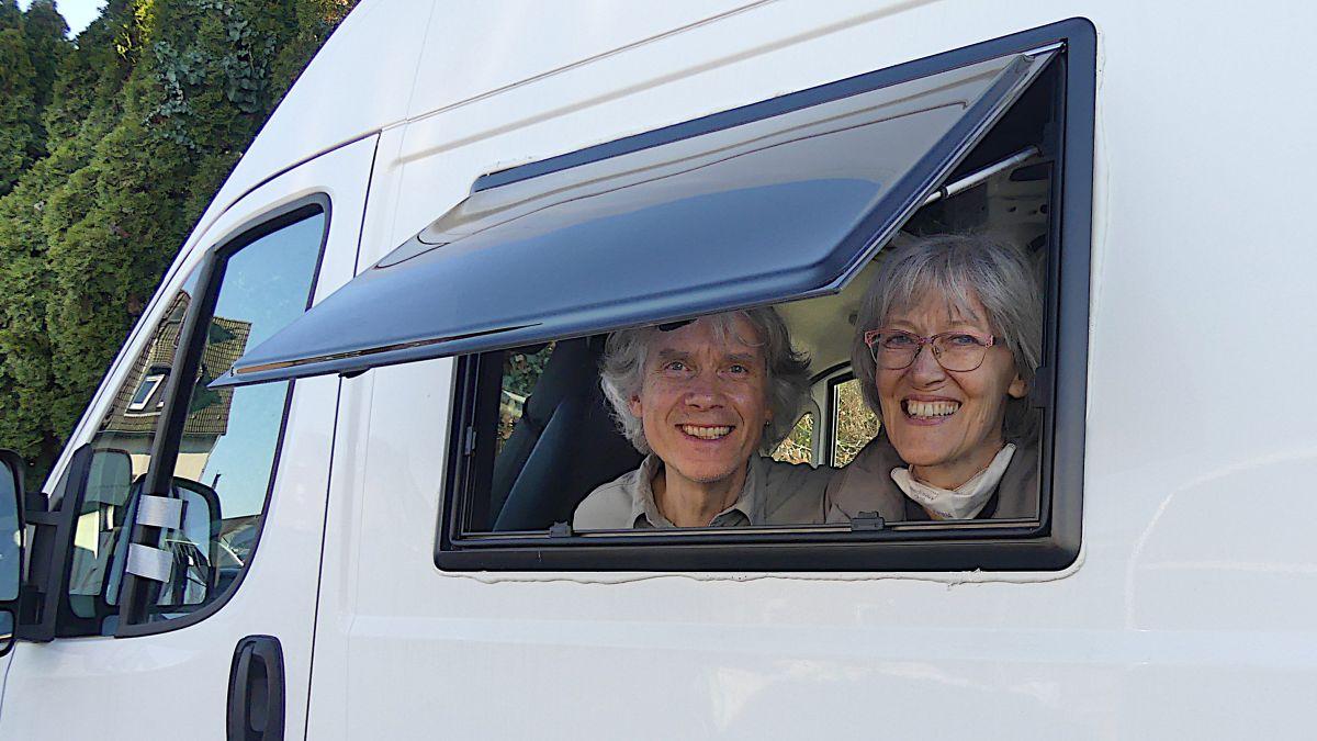 Gina und Marcus schauen aus dem Ausstellfenster des Kastenwagens.