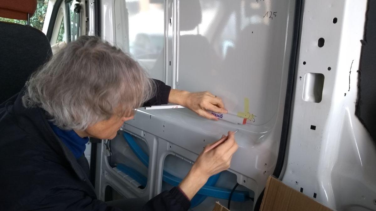 Marcus mit Zollstock und Stift beim Markieren des Ausschnitts für das Kastenwagen-Fenster.