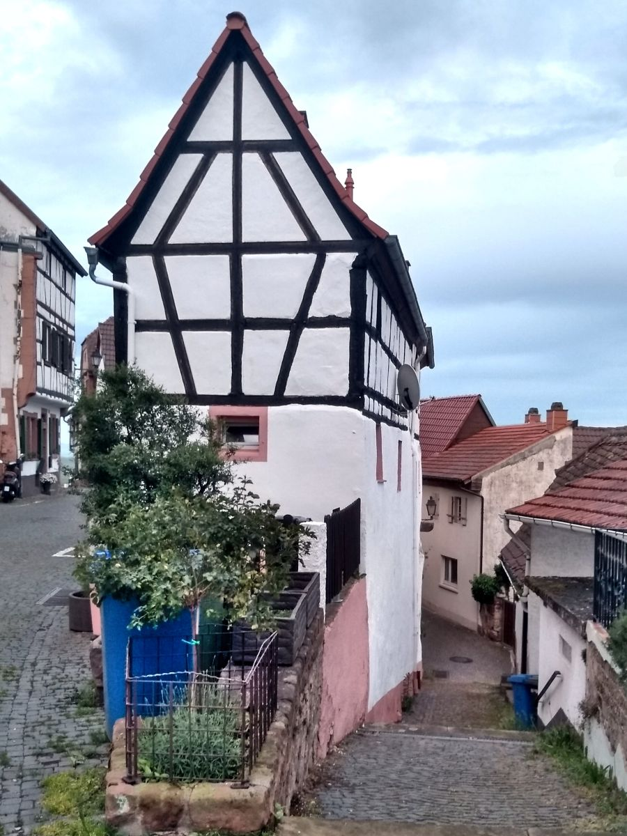 Schmales Fachwerkhaus mit spitzem Dach.