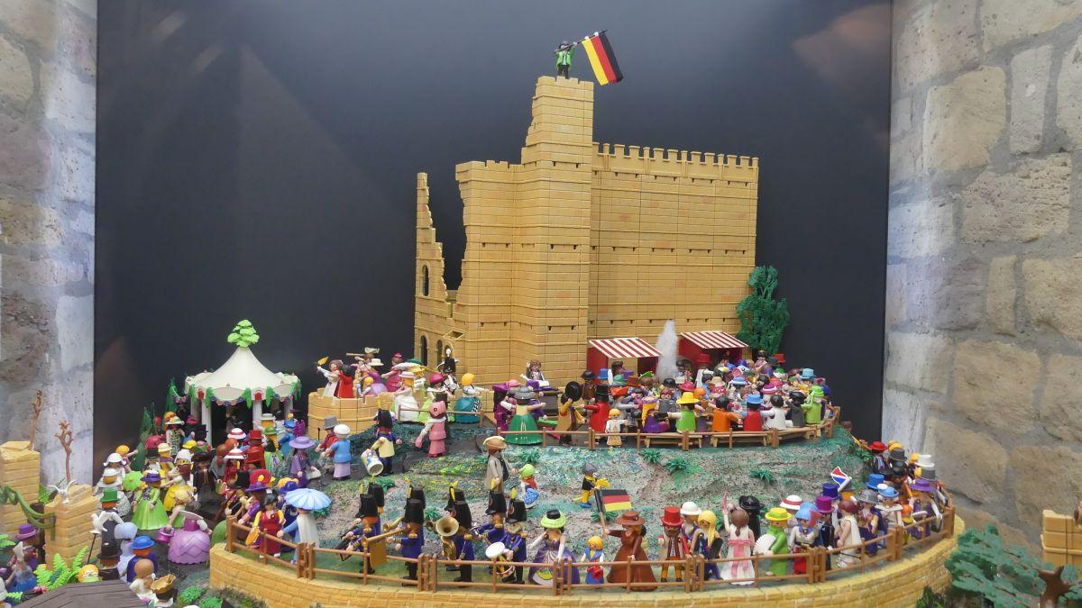 Playmobil-Figuren vor Modell-Schloss.