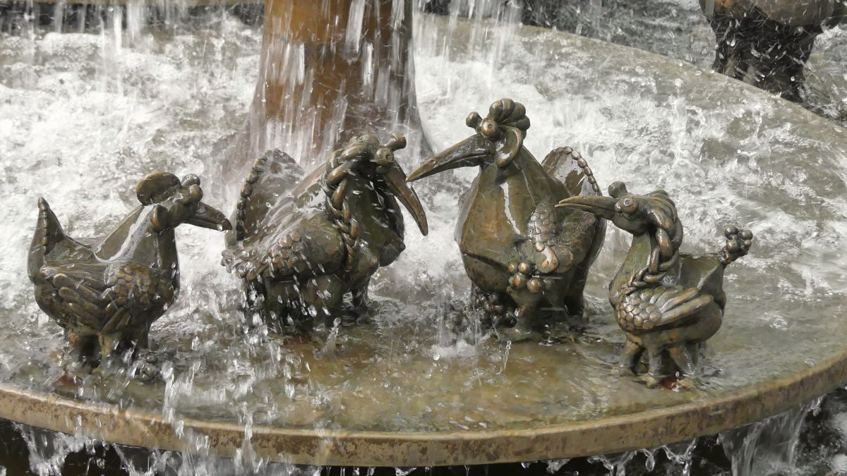 Fantasievögel in sprudelndem Brunnen.