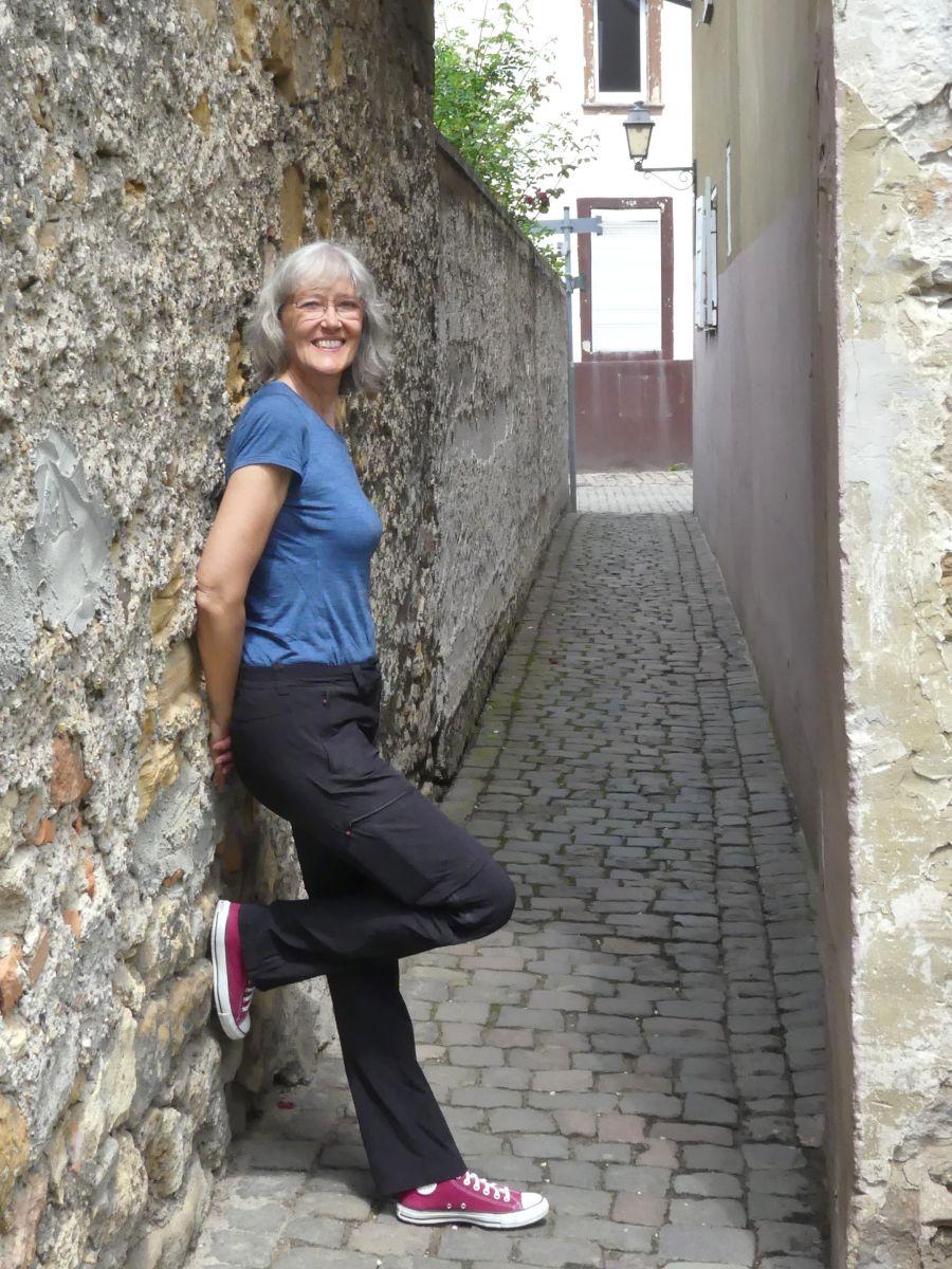 Gina lehnt an der Stadtmauer.