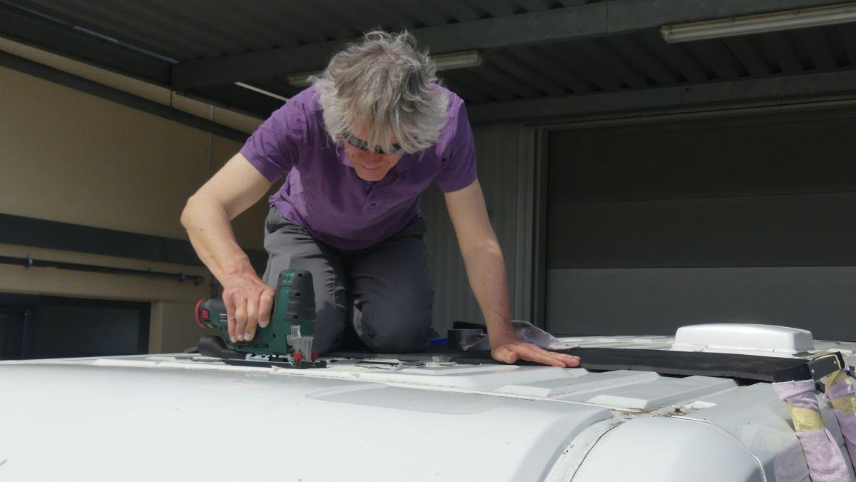 Marcus kniet auf dem Dach des Kastenwagens und sägt die Öffnung für die Dachluke.