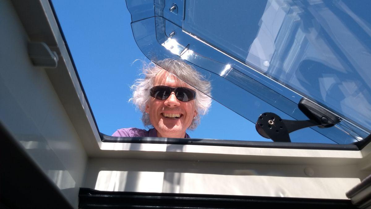 Marcus schaut von oben in die geöffnete Dachluke.