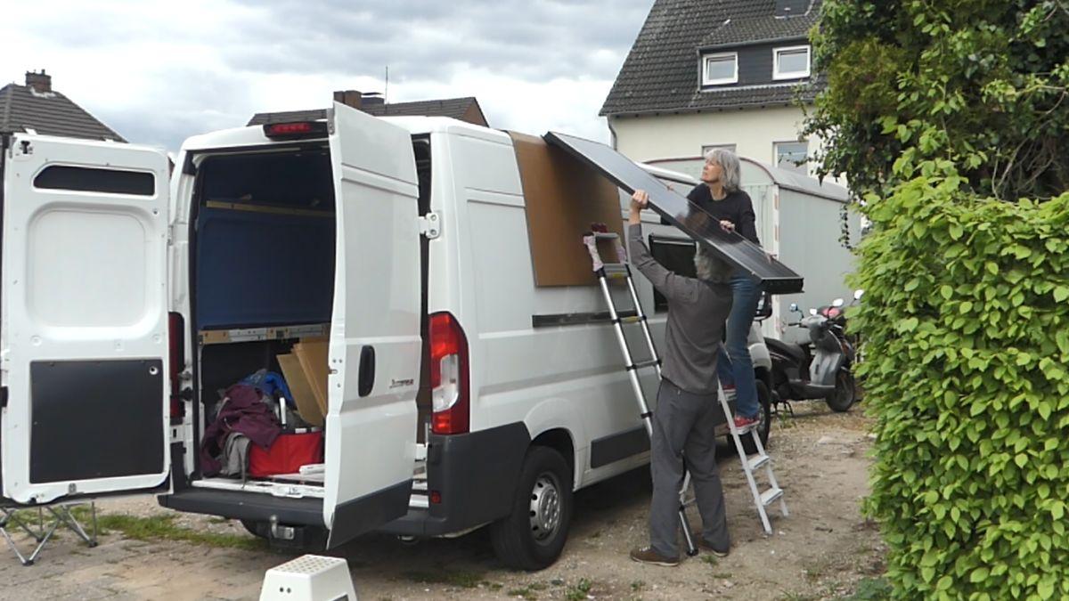 Gina und Marcus schieben das Solarmodul aufs Dach des Kastenwagens.