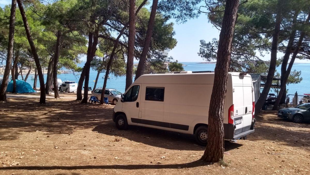 Camper unter Pinien vor dem blauen Meer.
