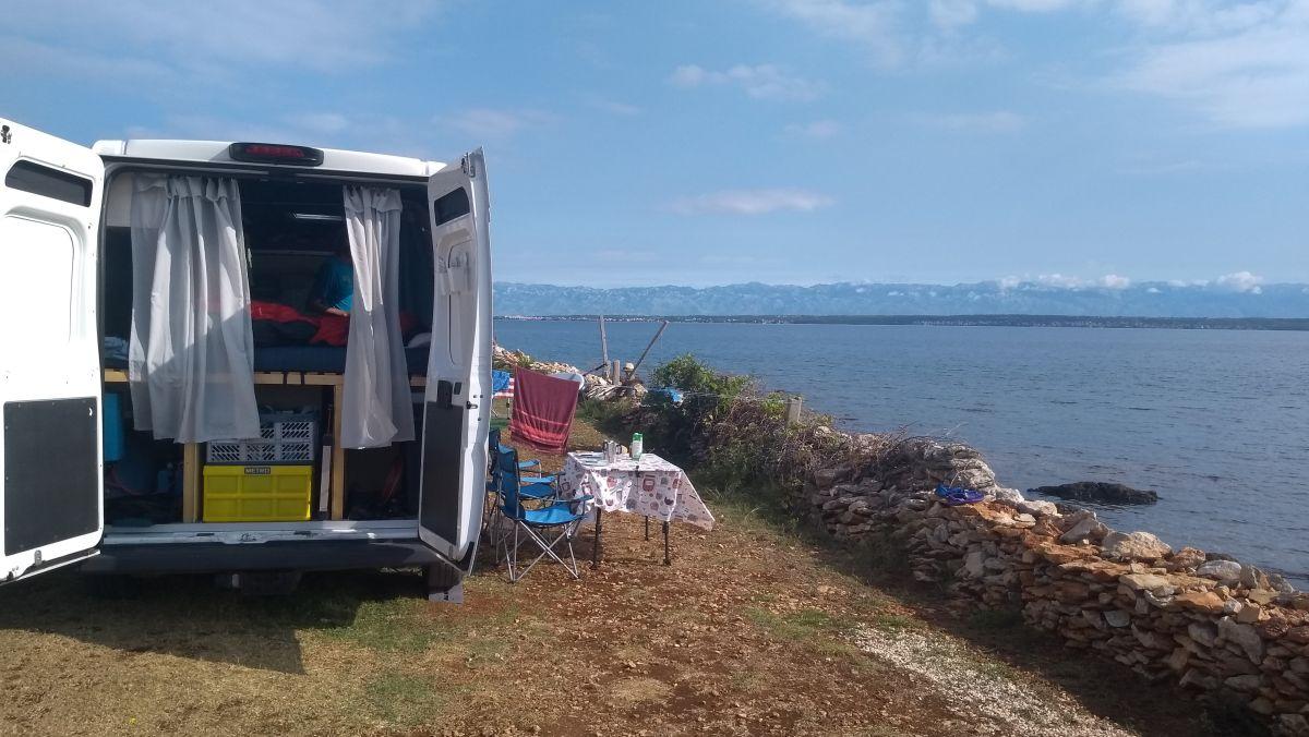 Camper steht am Ufer des Meeres.