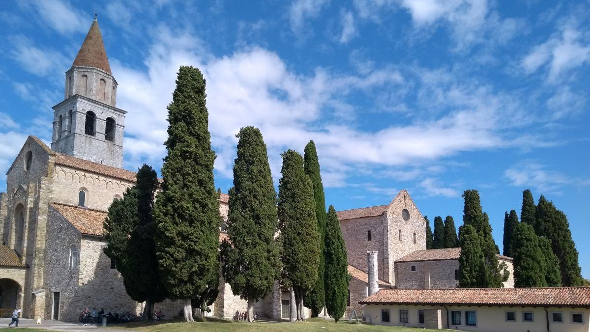 Kirche hinter hohen Zypresssen.
