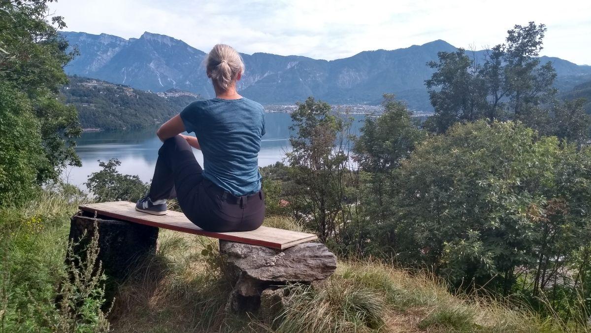 Gina sitzt auf einer Bank und schaut auf den See.