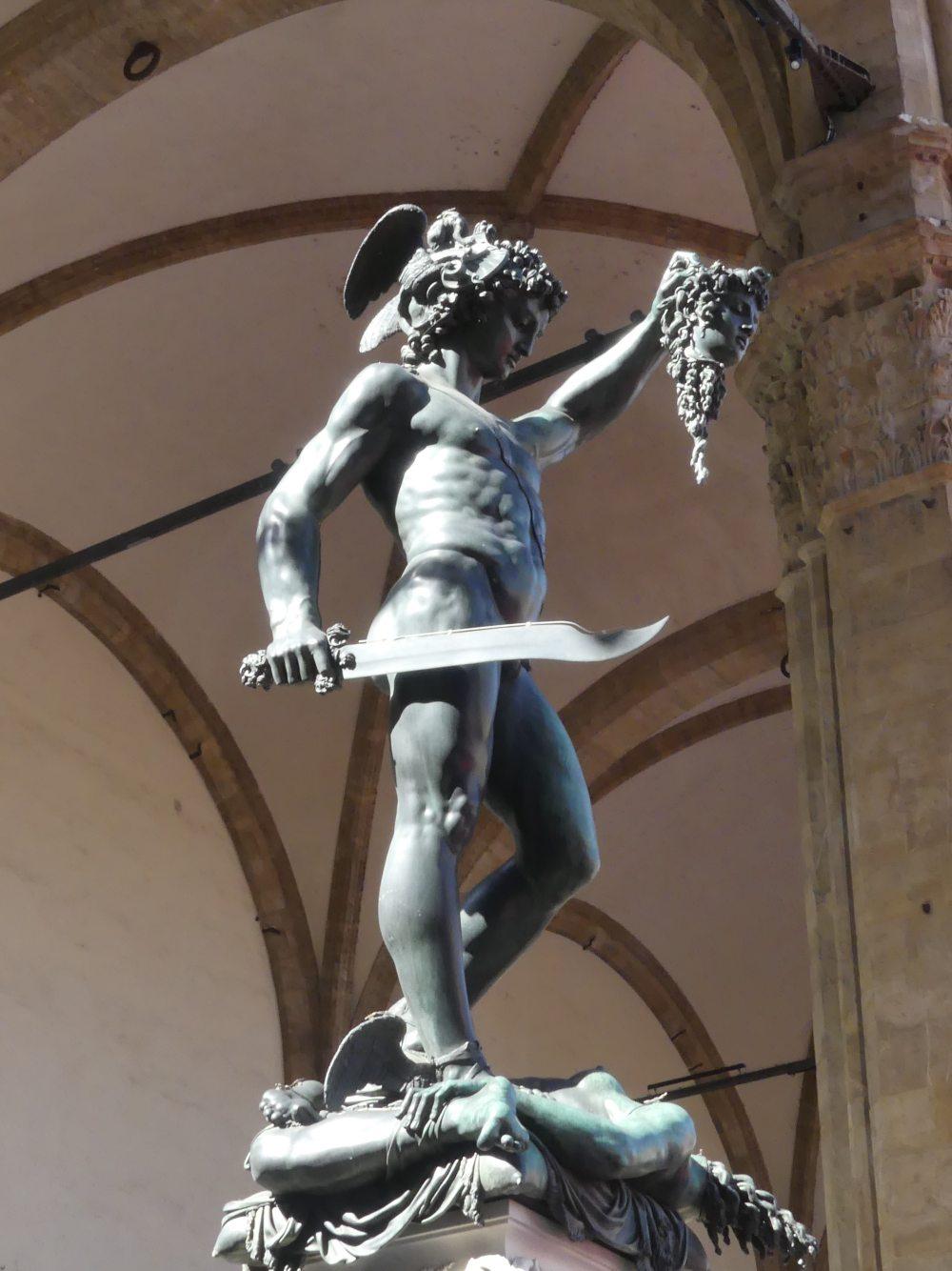 Bronzestatue hält abgeschlagenen Kopf hoch.