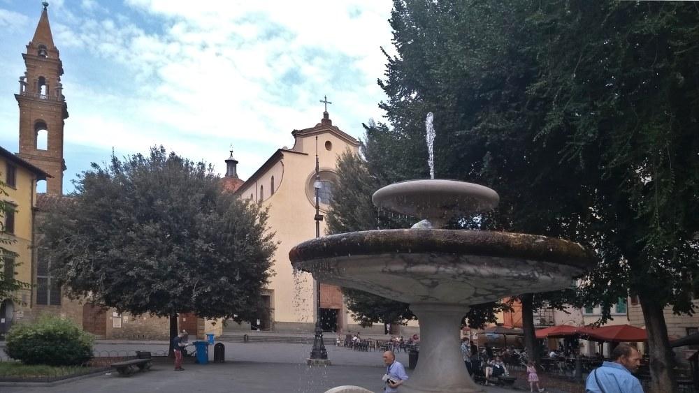 Platz mit großem Brunnen im Vordergrund, hinten steht eine Kirche.