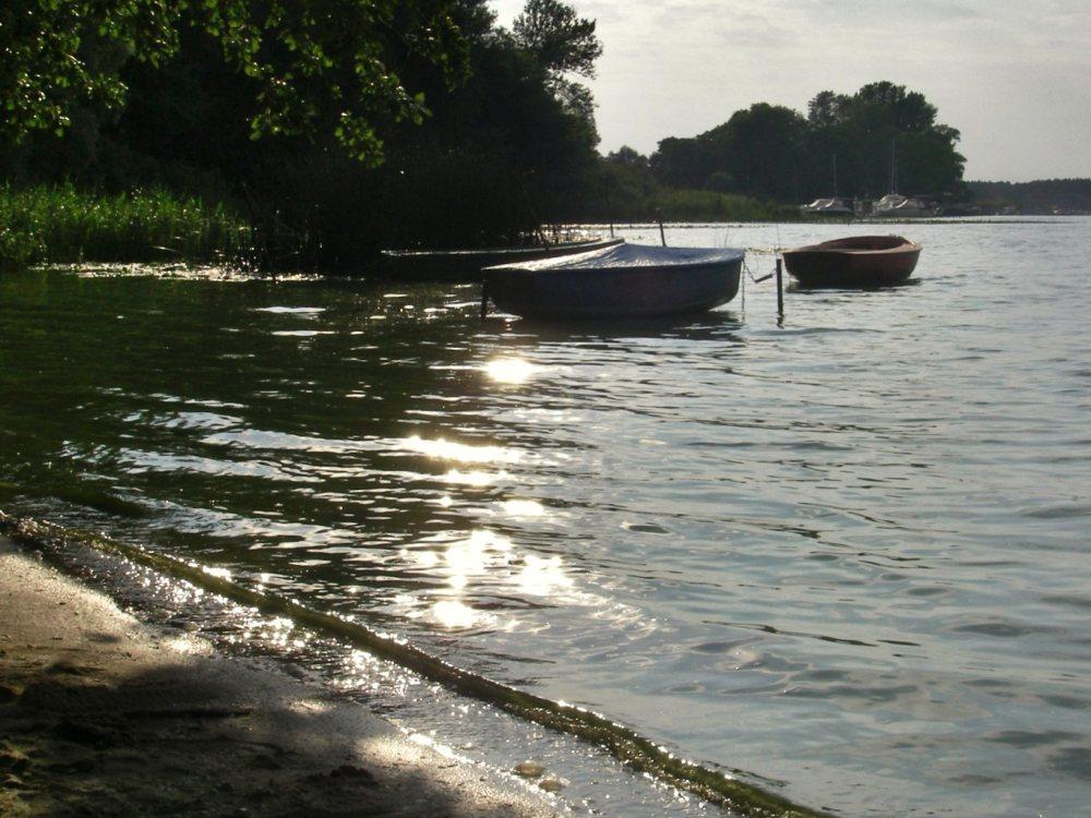 Zwei Boote liegen im Abendlicht im See.