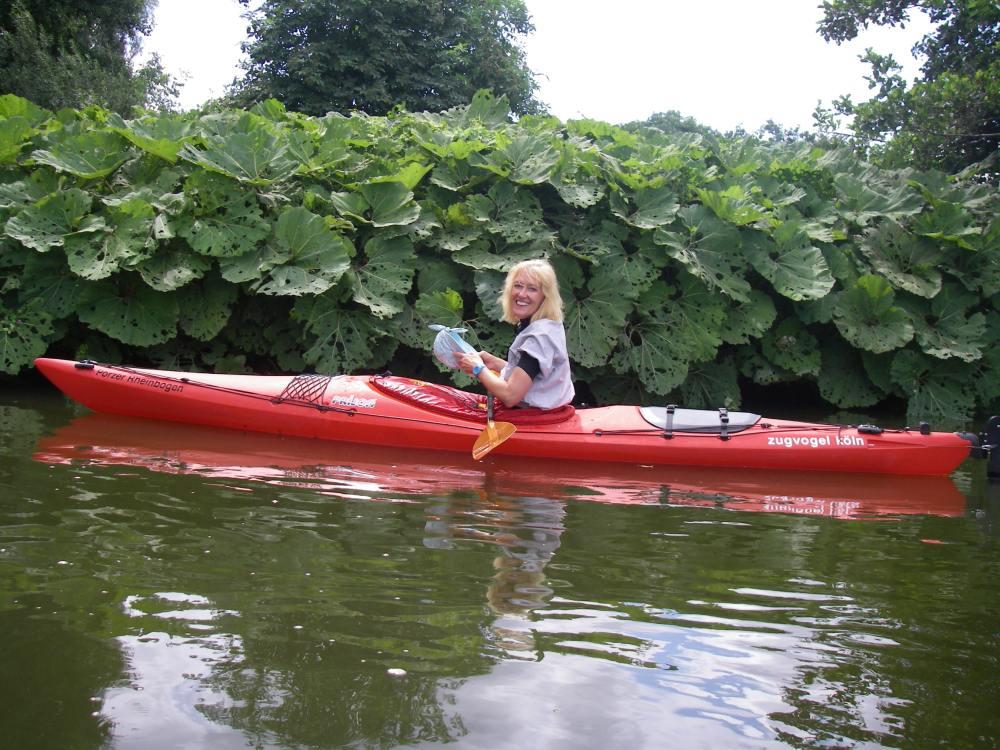 Gina vor großblättrigen Uferpflanzen.