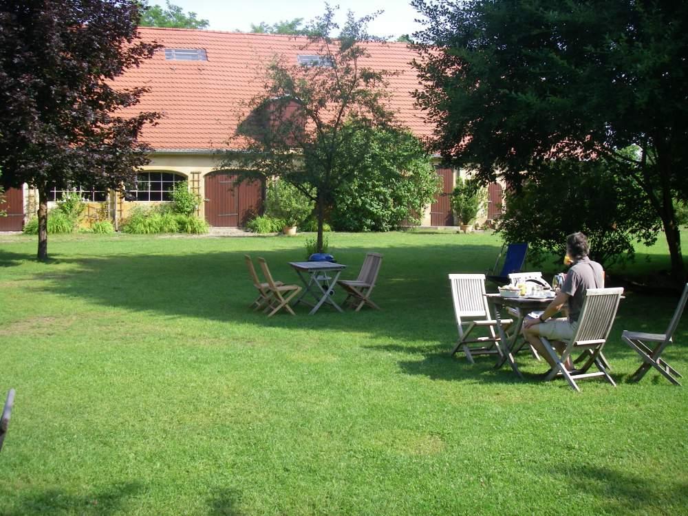 Großer Garten am Gutshof mit Frühstückstischen.