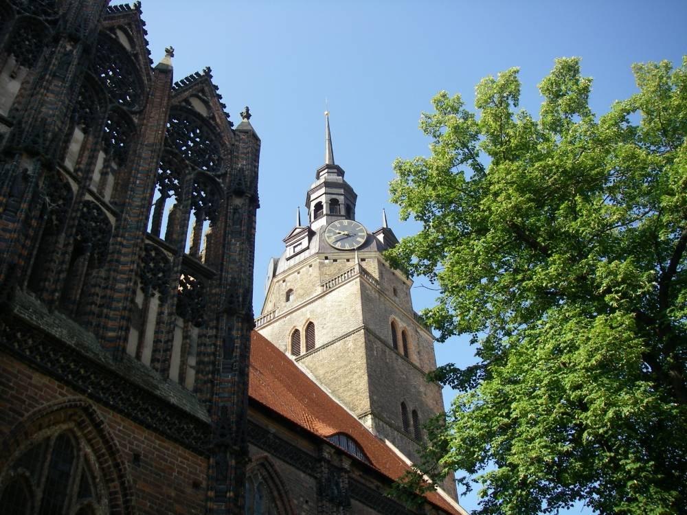 Kirchturm und gotische Fassade.