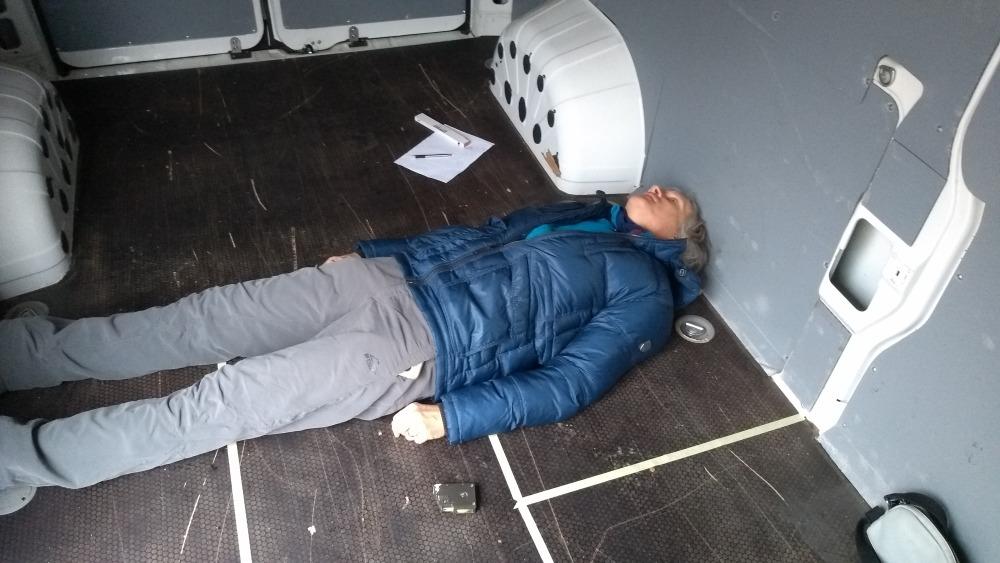 Marcus liegt quer im Kastenwagen auf dem Boden.