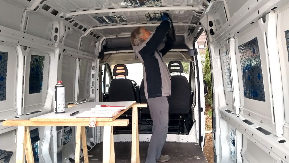 Marcus steht im Van und klebt Alubutyl an die Decke.
