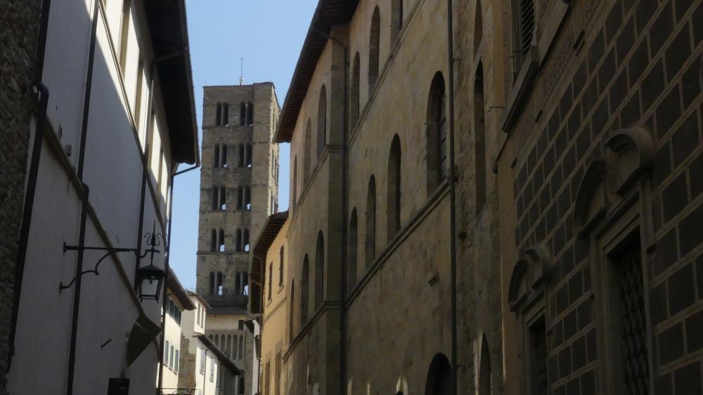 Durch eine Gasse sieht man den quadratischen Kirchturm mit vielen Fenstern.