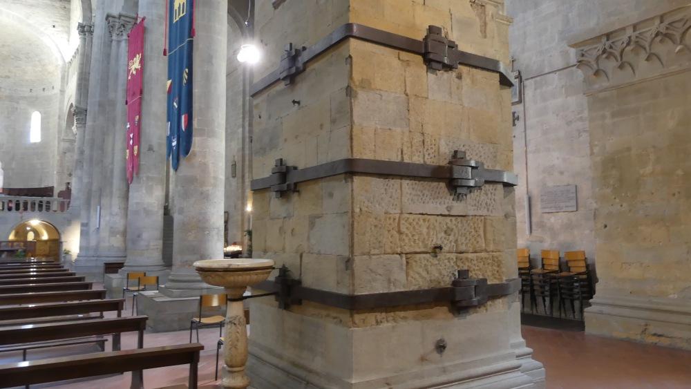 Eckiger Pfeiler, der von Eisenbändern zusammengehalten wird.