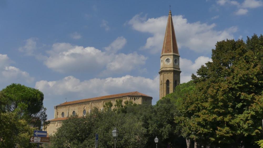 Turm und Kirchenschiff ragen über grüne Bäume hinaus.