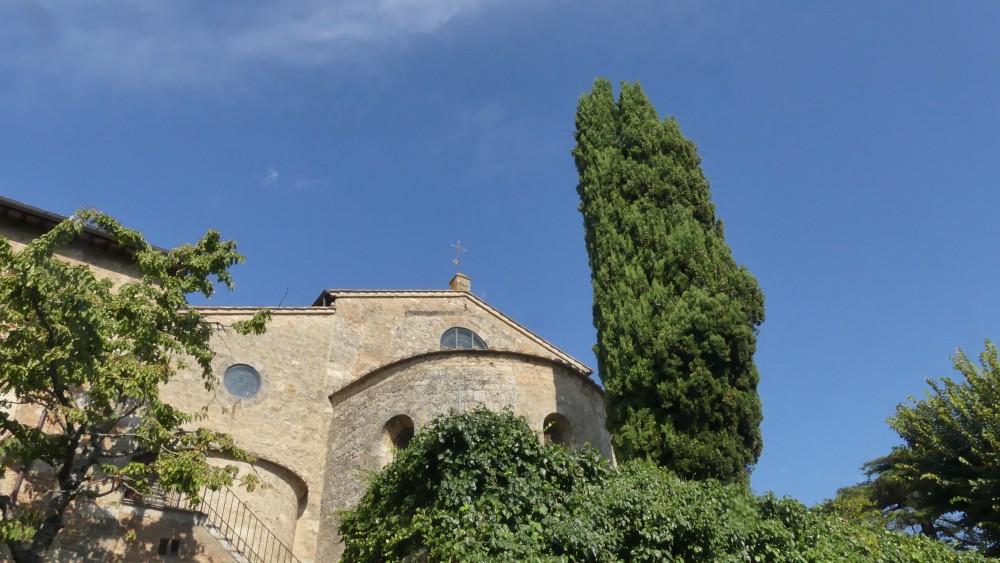 Apsis der Kathedrale von außen, rundherum stehen Zypressen.