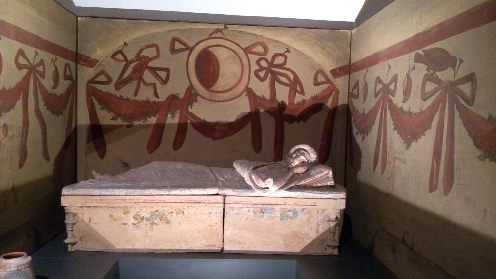Sarkophag in Kammer mit bemalten Wänden.