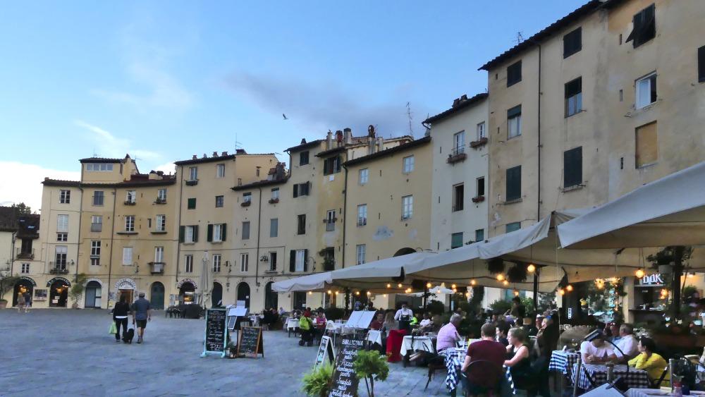 Piazza Anfiteatro mit vielen Restaurant-Tischen.