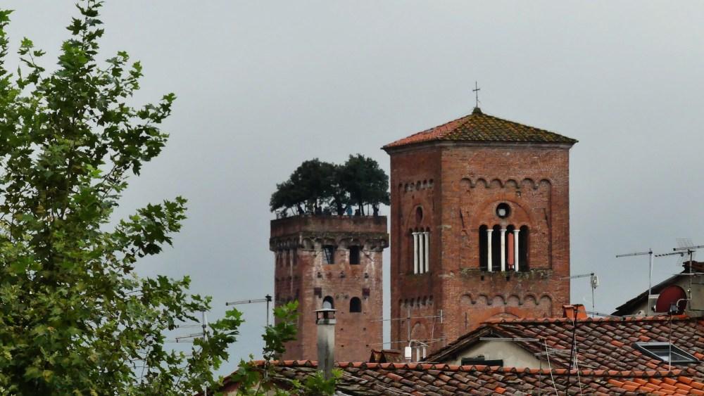 Kirchturm aus Backstein, dahinter Turm mit Bäumen oben drauf.