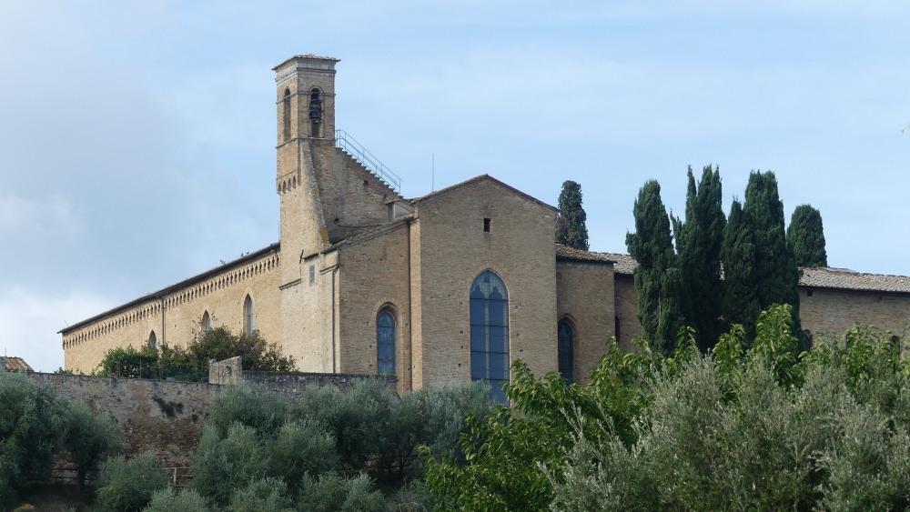 Schlichte gotische Kirche auf einem grünen Hügel.
