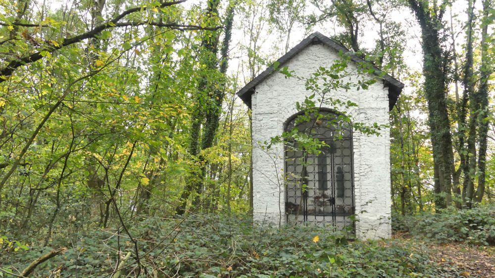 Kleine weiße Kapelle im Wald.