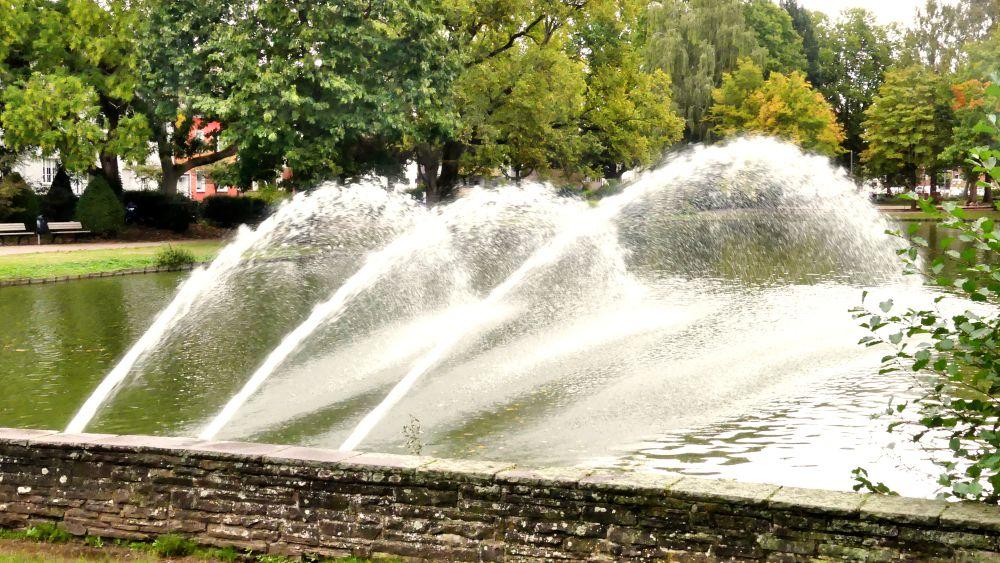 Drei flache Fontänen sprühen übers Wasser.