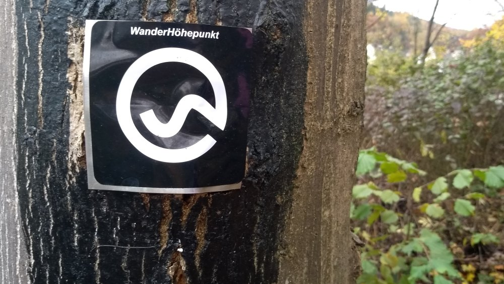 Wanderzeichen an einem Baum: Weißes Zeichen auf schwarzem Hintergrund.