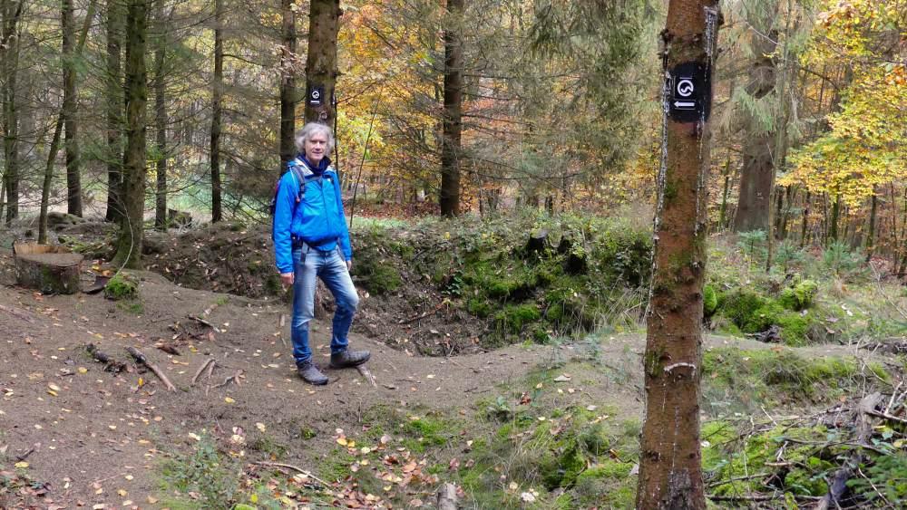 Marcus steht neben großen Vertiefungen im Wald.