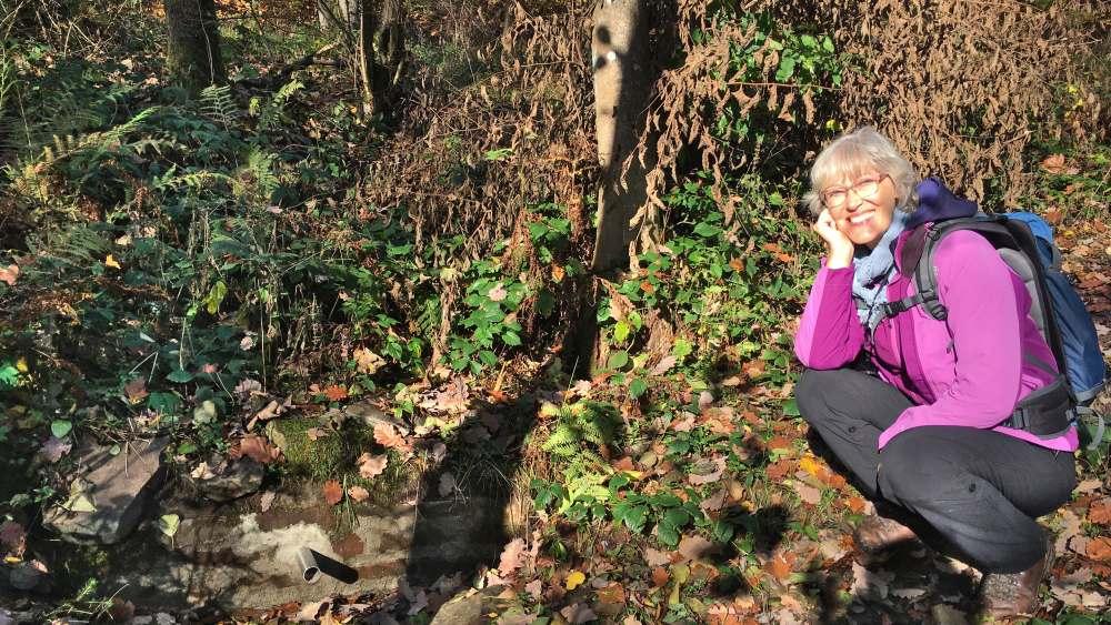 Gina hockt neben der trockenen Quelle des Achenbachs.