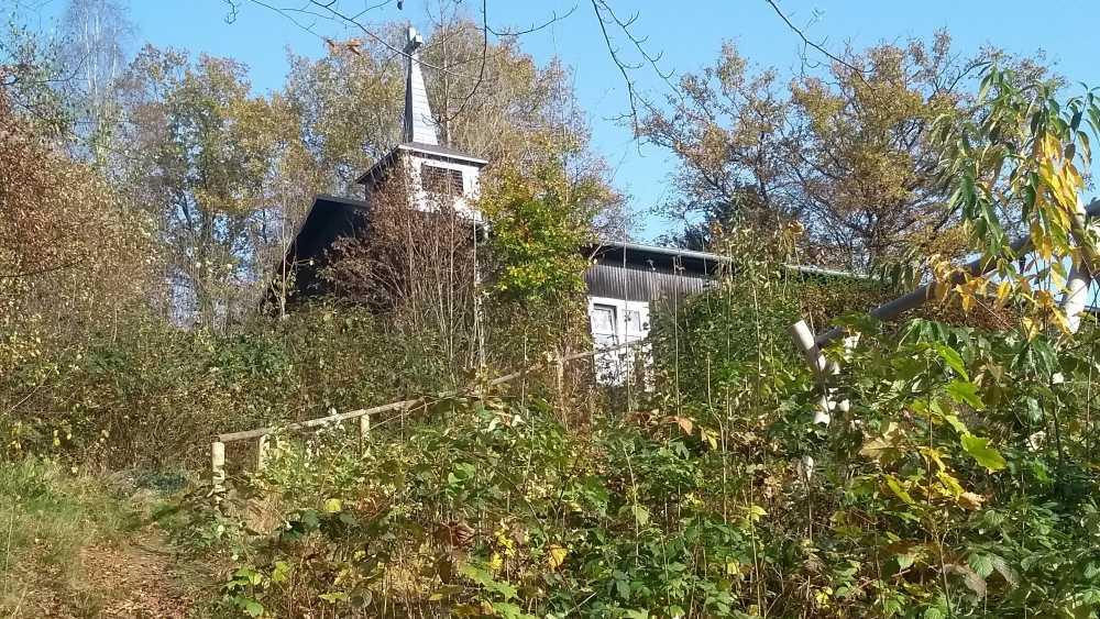 Kleine Holzkirche auf einem Hügel.