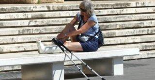 Frau mit Gipsbein und Krücken sitzt auf einer Bank.